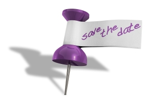 A purple thumbtack with a tape tag and the words save the date written in purple marker